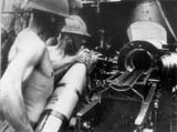 Gunners operating a 150mm Skoda M1934 heavy field howitzer. They are wearing Adrian M1916 helmets, specific of auxiliary troops. Bessarabia, July 1941.